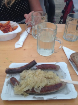 Bratwurst and sauerkraut; the drink is a pint of white wine with sparkling water
